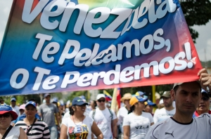 Credit: Flickr, Riccardo Vásquez. Opposition activists hold signs saying they will fight for Venezuela rather than lose their country, as mediation talks begin.